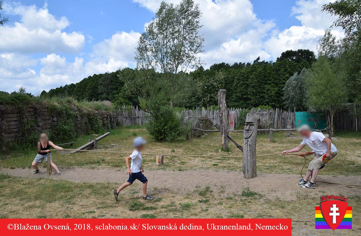 Rodinná zábava. Rodičia s deťmi sa preťahujú za lano prechádzajúce cez stred drevenej modly. Pekné skĺbenie minulosti a súčasnosti.